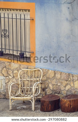 White old empty chair on a blue wall. Domestic house