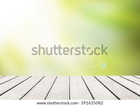White old wood floor with blurred green leaves background. Wooden planks stage and blur leaf with flare sunlight. Abstract medical backdrop. Focus to table top in the foreground. Sun rays blur bokeh. - stock photo