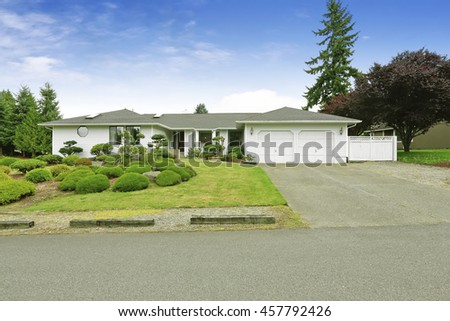 White one story house with nice landscape design. Green lawn, shrubs and decorative trees. Northwest, USA - stock photo