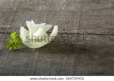 White Onion Slices and parsley on wooden board - stock photo