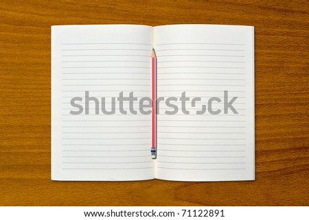 White open notebook and pencil on beech wood background.