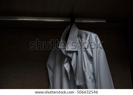 white or beige alone shirt hanging on rack in built-in cupboard. dark night scene