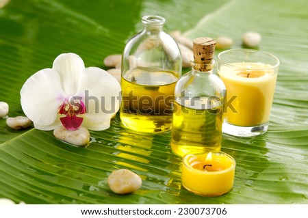 White orchid and stones, oil, candle on wet banana leaf - stock photo