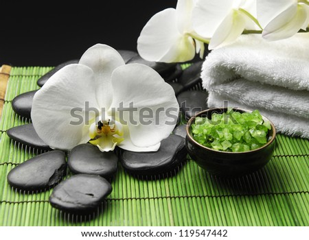 white orchid with pebble stone and towel green salt in bowl on green mat