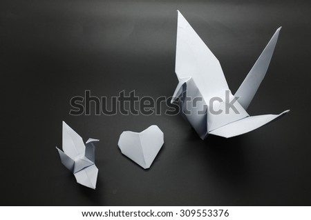 White origami crane and heart between, bird paper