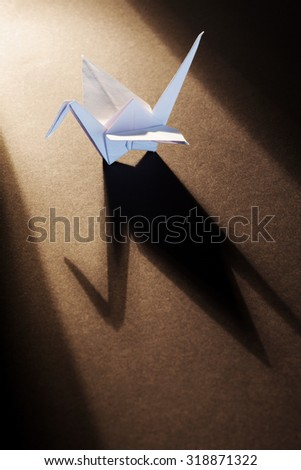 White origami crane isolated on wooden background with lights and shadows. - stock photo