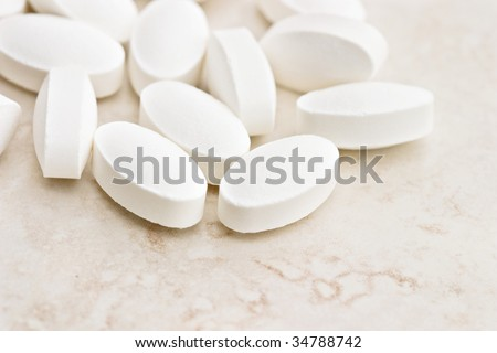 White oval pills spilled onto the counter. Shallow DOF. - stock photo