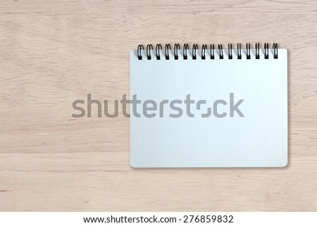 white page of notebook on wood texture background