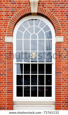 White painted wood arched window in a red brick wall