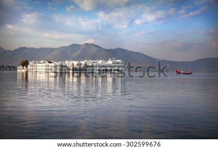 White palace and boat on Lake Pichola at cloudy sky in Udaipur, Rajasthan, India - stock photo