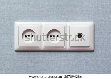 White panel of two electrical sockets and outlets for cable television on the wall with gray wallpaper - stock photo