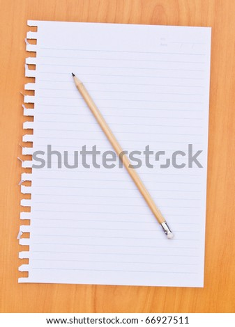 white paper and pencil on wood table - stock photo
