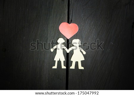 White paper couple silhouettes on wooden floor separated with he - stock photo