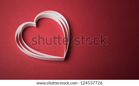 White paper heart on the red with copy space - stock photo