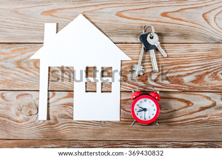 White paper house figure with keys and red alarm clock on wooden background. Real Estate Concept.