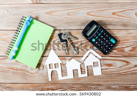 White paper house figure with keys, notebook and calculator on wooden background. Real Estate Concept.