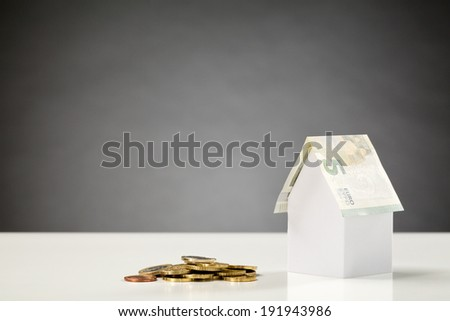 White paper house with a roof of a five Euro note next to a pile of Euro coins - a mortgage, loan or investment concept. - stock photo