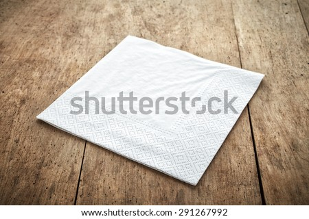 white paper napkin on old wooden table - stock photo