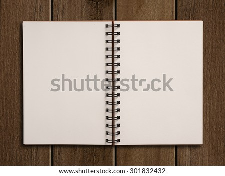 White paper notebook on wooden table.