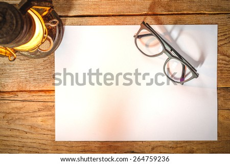 White paper on a wooden table with glasses, old lamp - stock photo