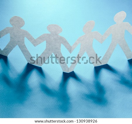 White paper people standing in a cycle and one orange paper man inside. Isolated on white background - stock photo