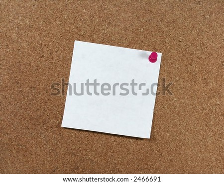 White paper pinned to a corkboard with a pink pushpin. - stock photo