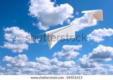 White  paper plane flying. Sky and clouds in the background