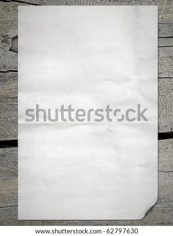 White paper pulled out from a notebook on a wood background - stock photo