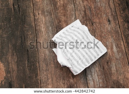 white paper sheet note rip and crumpled on a wooden  background  - stock photo