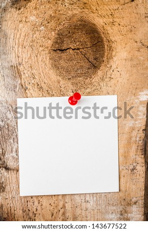 White paper sticky note reminder With red Push Pin on wooden old background