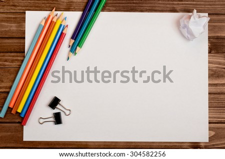 White paper with colorful pencil on wooden table - stock photo