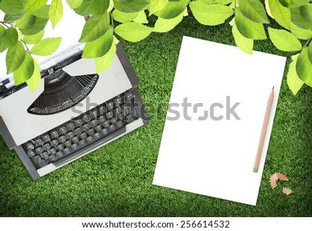 white paper with typewriter on Grass background ,  (Top view) - stock photo