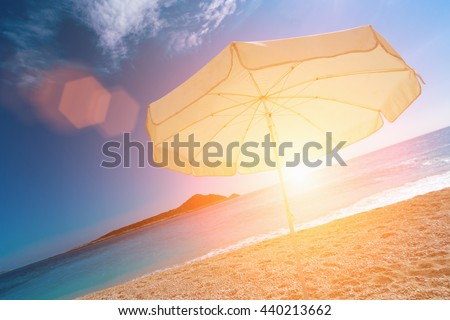 White parasol on a sandy beach in the sunlight - stock photo