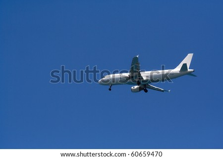 White passenger airplane in the blue sky - stock photo