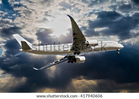 White passenger airplane is flies against the backdrop of sun and storm clouds - stock photo