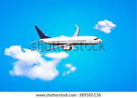 White passenger airplane with clouds on a blue background. The concept of travel - stock photo