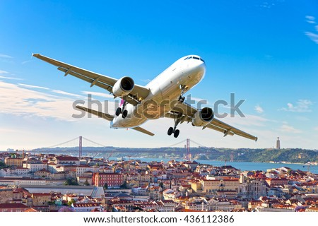 White passenger airplane with right roll. Aircraft is flying in the blue sky over the city rooftops, river and bridge. - stock photo
