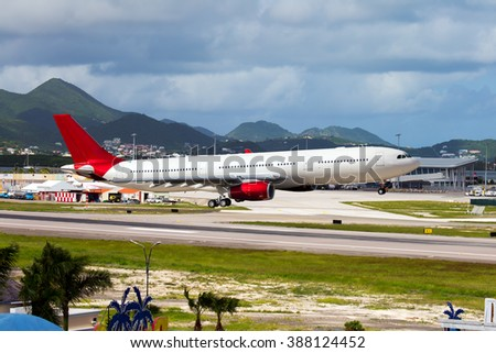 White passenger plane with a red Tail and red Engines. Aircraft is arriving at the airport. In the background is a huge mountains. - stock photo