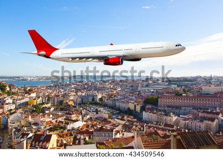 White passenger plane with a red Tail and red Engines. Aircraft is flying over the city. - stock photo