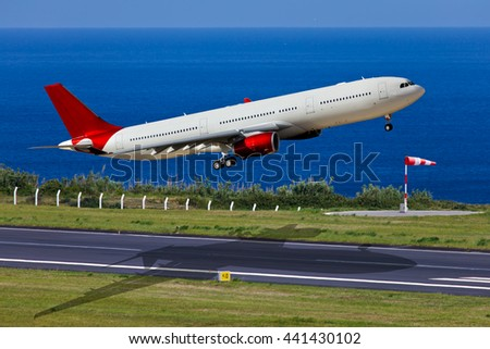White passenger wide-body airplane with red engines and red tail. A few seconds after take-off from the airport runway. Aircraft are climbing against the deep-blue ocean. - stock photo