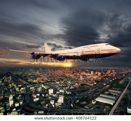 White passenger wide-body plane. Aircraft is flying in the sunset cloudy sky, over the over city residential areas and skyscrapers. - stock photo