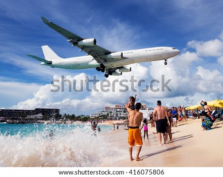 White passenger wide-body plane in the blue cloudy sky. Aircraft is flying low over the beach, sea and swimming tourists. - stock photo