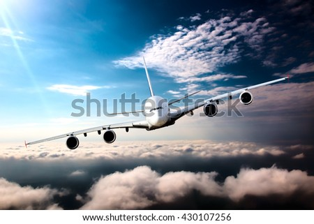 White passenger wide-body plane with left roll. Aircraft is flying in the blue sky over the the clouds. - stock photo