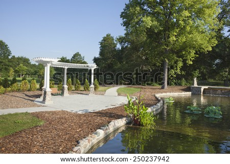White pavillion, walkway and pond in morning light at Como Park in Saint Paul, Minnesota - stock photo