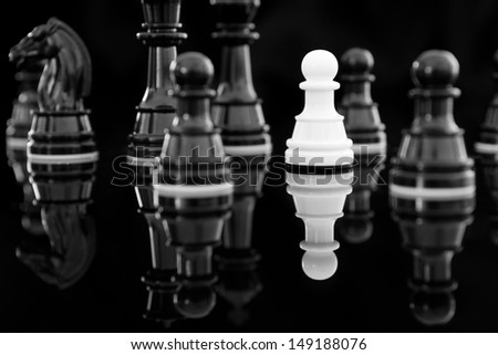 white pawn among black chess - stock photo
