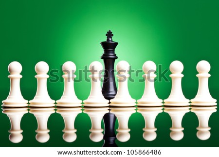white pawns in front of a black king - chess pieces on green background - stock photo