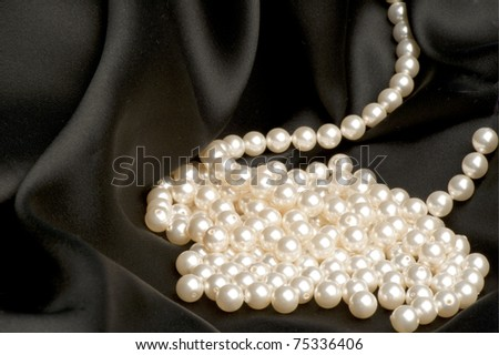 White pearls on a black satin fabric