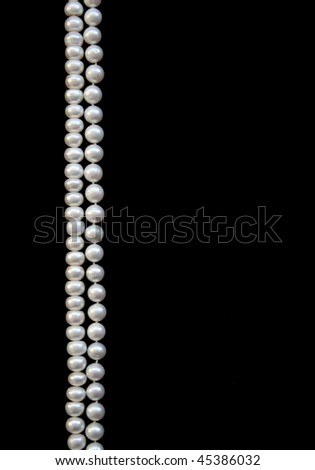 White pearls on the black silk as background - stock photo