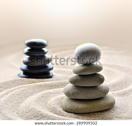 White pebbles stones stacked inside raked circle in zen garden with black stones outside
