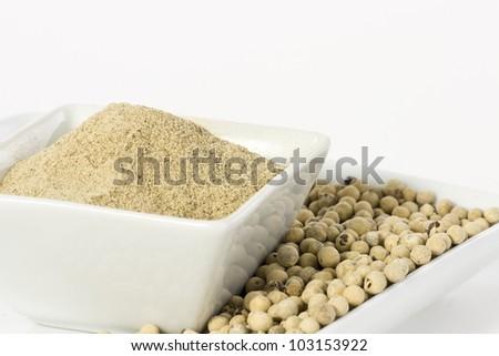 White pepper grain and powder on ceramic bowl - stock photo